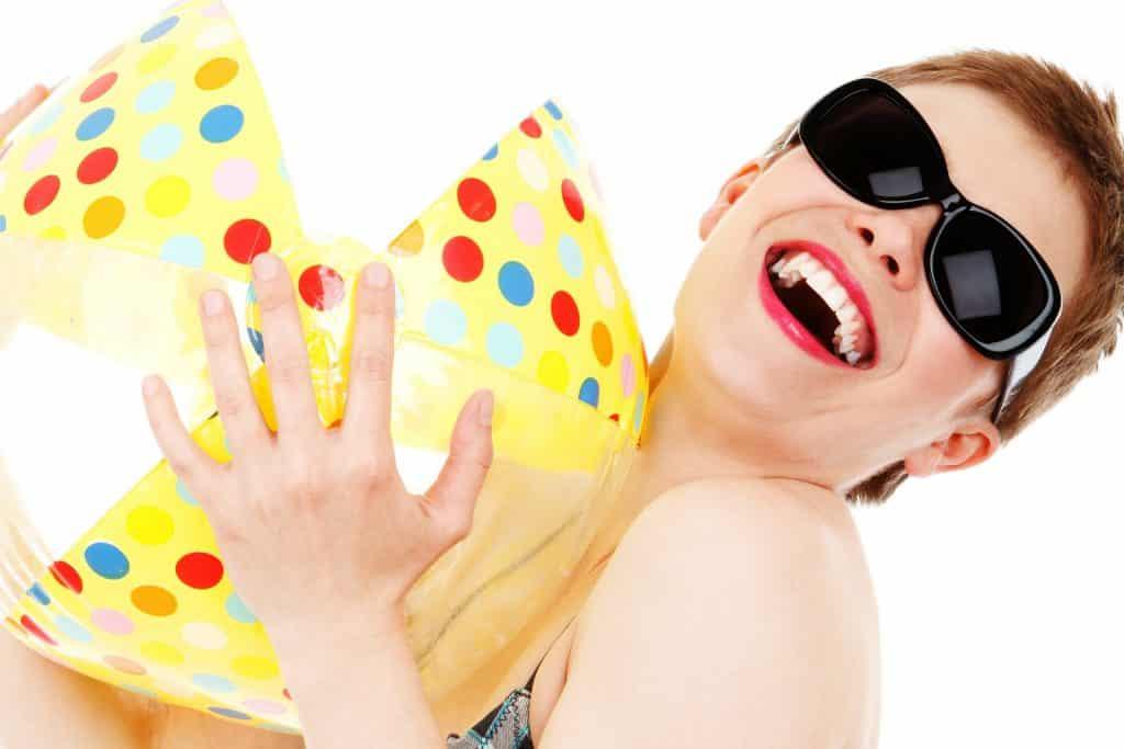 Imagem de uma mulher de cabelos ruivos e curtos. Ela usa um óculos escuro, sorri muito e segura em suas mãos um bola grande colorida. Ela aparenta ter um bom caráter.