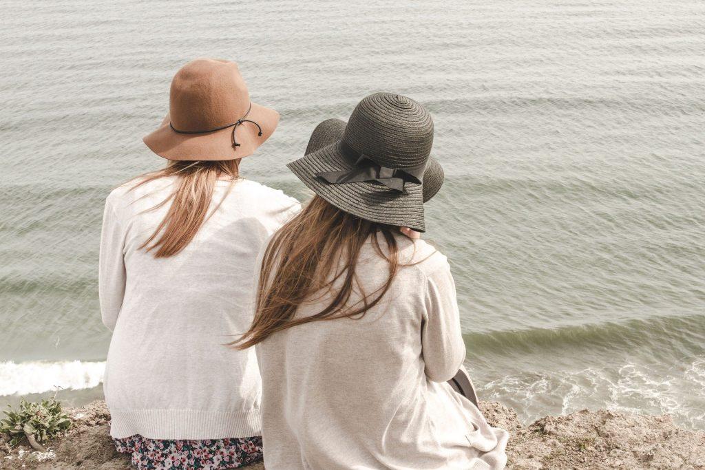 Duas mulheres sentadas à beira do mar. Elas estão de costas olhando para ele. Ambas usam um chapéu de sol e usam uma blusa de linha leve.