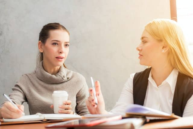 Mulheres conversando em mesa de trabalho
