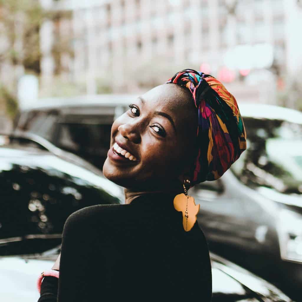 Mulher negra sorrindo com lenços colorido na cabeça