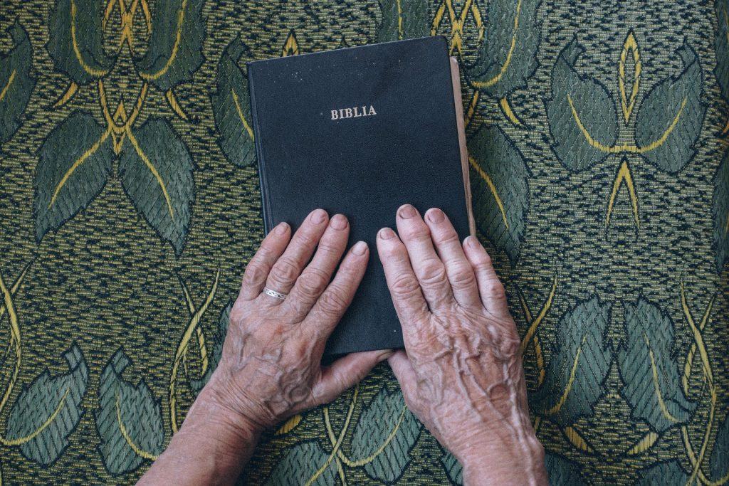 Imagem da bíblia fechada e sobre ela as mãos de uma senhora idosa. Ela está exercendo a sua espiritualidade.