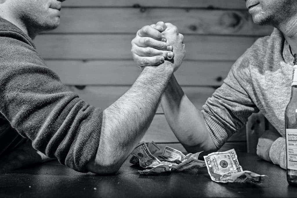 Dois homens sentados em uma mesa apostando dinheiro em uma queda de braço.
