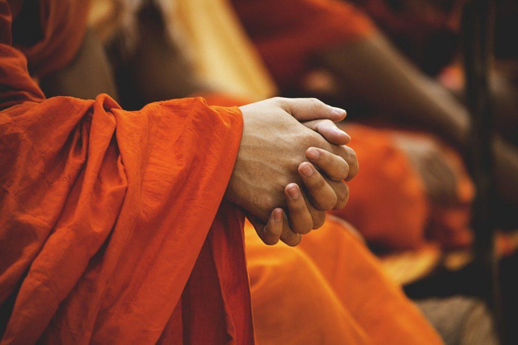 Imagem das mãos de uma pessoa adepta ao budismo. Ele está em oração exercitando a espiritualidade.