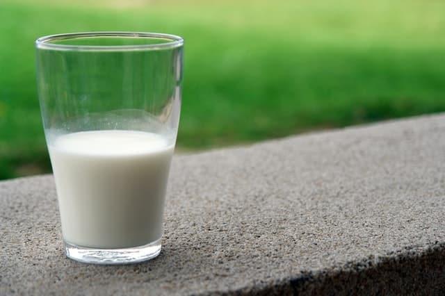 Copo de vidro com leite até a metade em foco