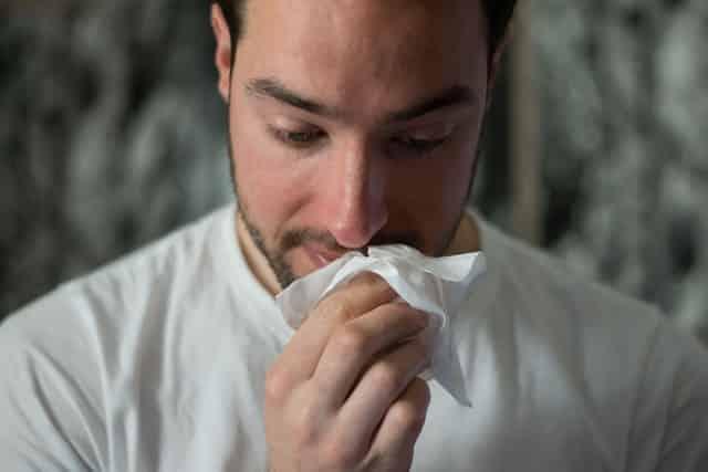 Homem com papel higiênico limpando nariz
