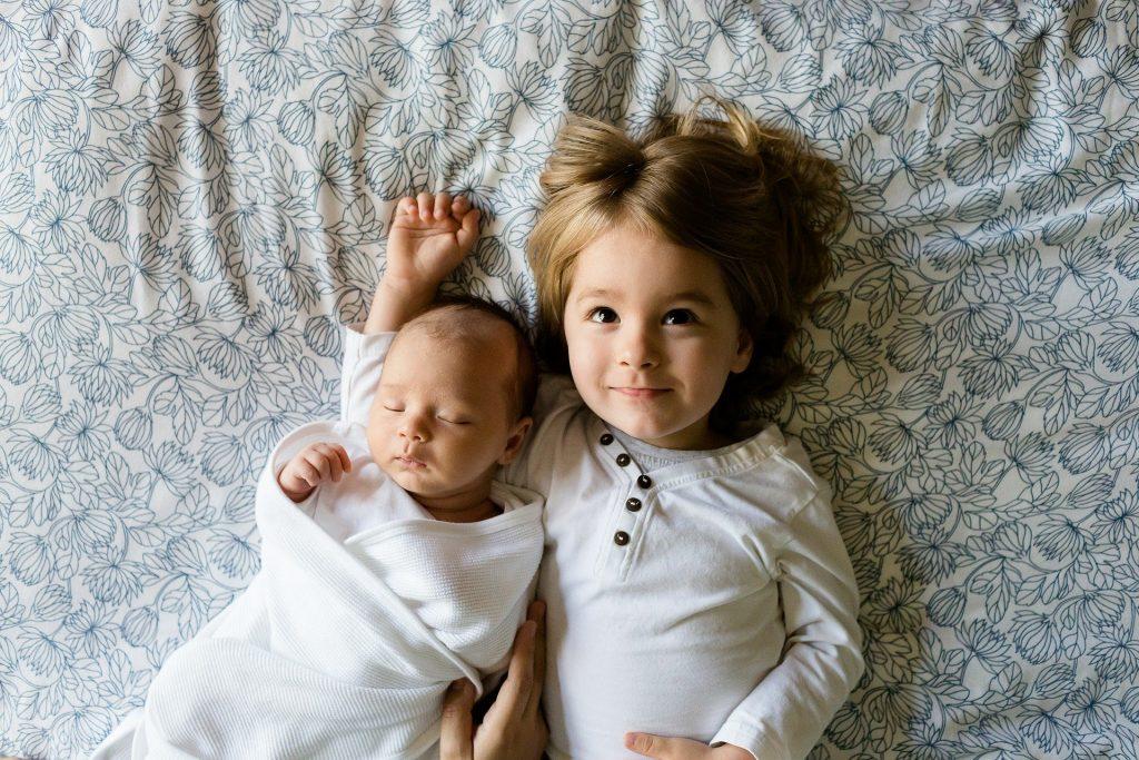 Imagem de dois irmãos, sendoo um recém nascido e uma maior, deitados sobre a cama.