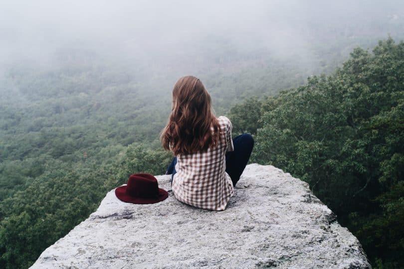 Mulher sentada em uma rocha na montanha olhando para frene com seu chapéu ao lado