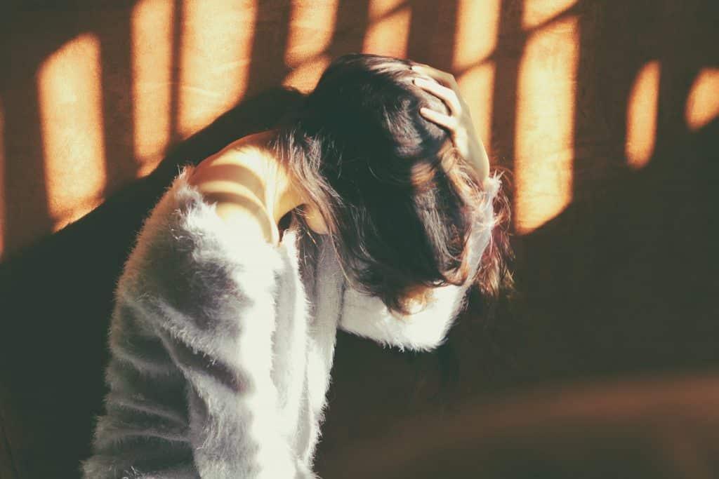 Mulher sentada no chão ao lado de uma parede com sua mão na cabeça