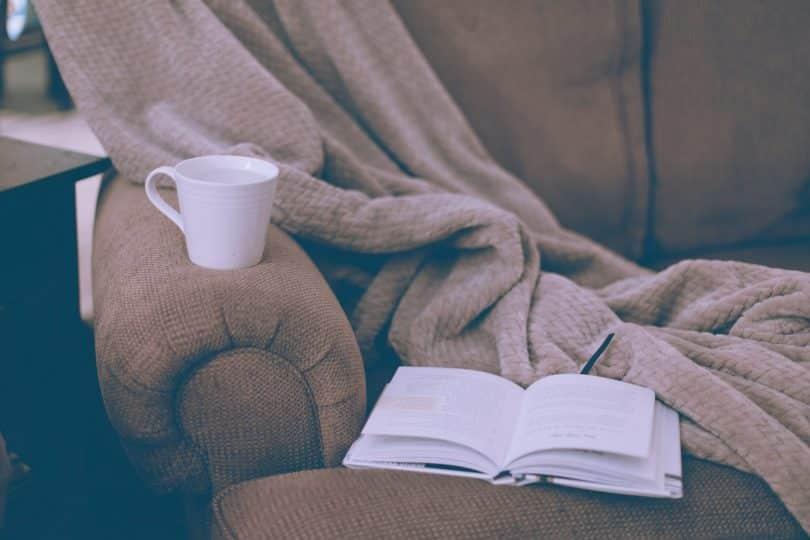 Sofá com livro aberto, caneca e cobertor