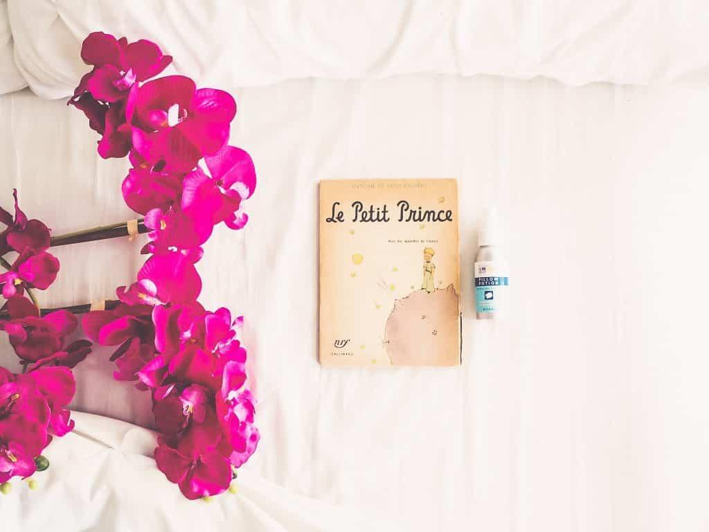 Livro O pequeno príncipe em umacama ao lado de flores e um pequeno frasco