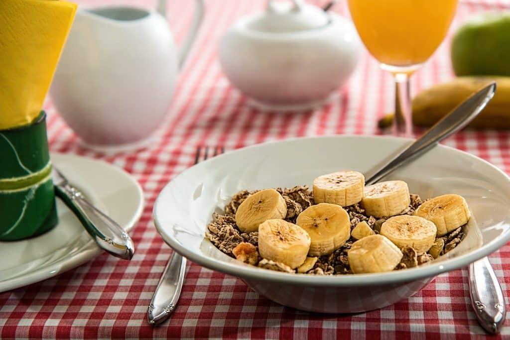 Imagem de um prato de cereais com bananas picadas. Ele está servido sobre uma mesa com toalha quadriculada nas cores vermelho e branco. Ao lado do prato um copo de suco de laranja.