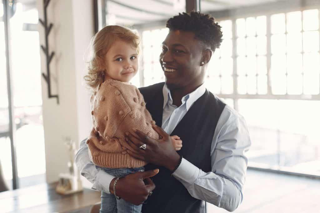 Homem de roupas sociais segurando uma criança em seu colo.