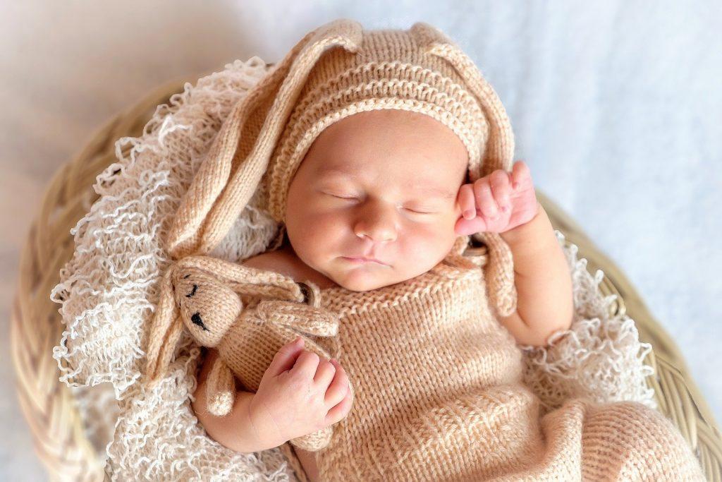 Imagem de um bebê vestido com uma roupa de coelho de lã, deitado em um cesto de palha. Ele está dormindo e segura em sua mão um coelho de lã.