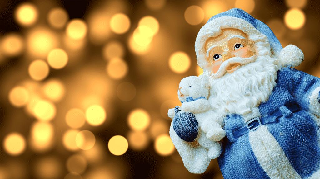 Imagem de um lindo boneco de papai noel vestindo uma roupa azul e segurando em uma de suas mãos um ursinho de pelúcia branco.