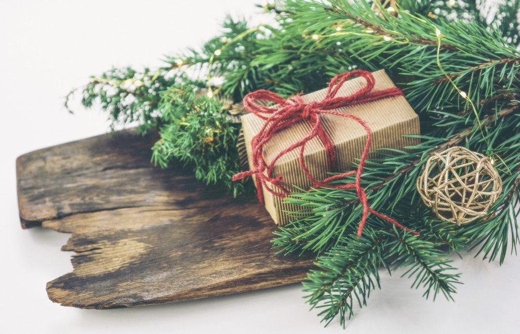 Imagem de um presente de Natal em uma caixa de papelão pequena embrulhada com um laço de linha na cor vermelho. A caixa está sobre uma madeira decorada com folhas da árvore de Natal.
