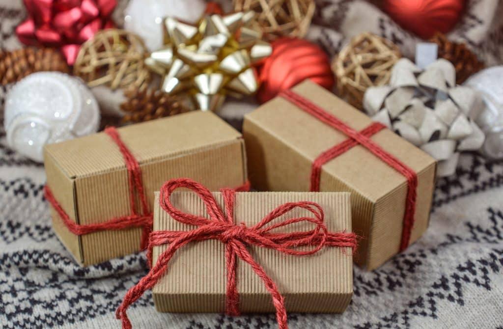 Imagem de três caixas pequenas de papelão de presente de Natal embrulhadas com uma linha vermelha e um laço, sobre uma mesa com toalha de renda branca e enfeites natalinos.