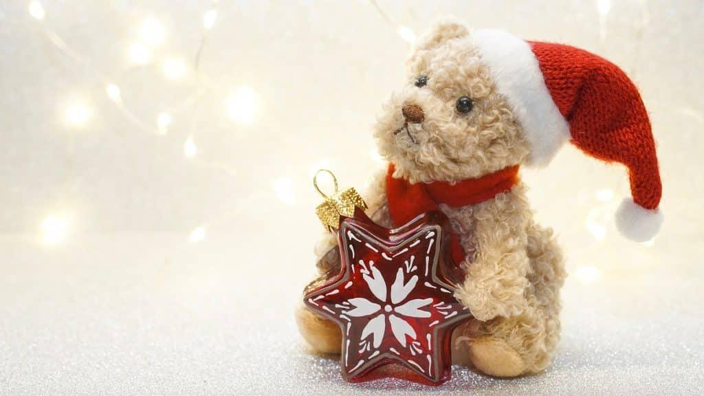 Imagem de  um lindo e pequeno ursinho de pelúcia vestindo uma touca de papai noel e segurando em suas mãos um pingente em formato de estrela vermelha para colocar na árvore.