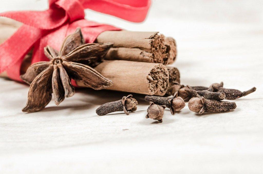 Imagem de canela e cravos que ajudam a aumentar a libido. Eles estão envoltos de uma fita com laço vermelho.