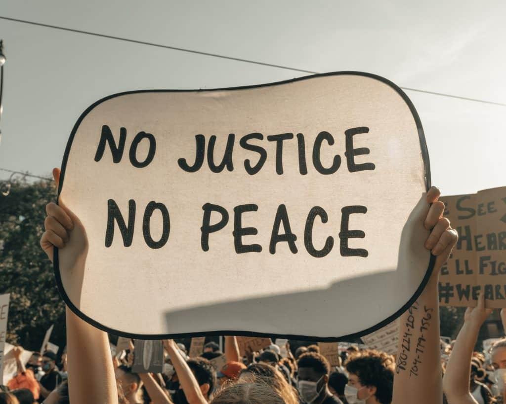 """Pessoas protestando contra o racismo e uma mulher segurando cartaz escrito """"sem justiça sem paz"""""""