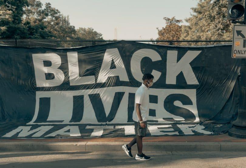 """Homem usando máscara de proteção no rosto andando em frente a uma faixa na rua escrito """"vidas negas importam"""""""