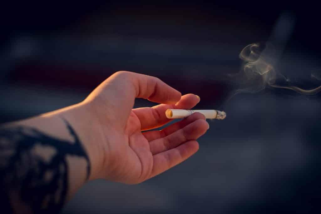 Mão branca segurando cigarro.
