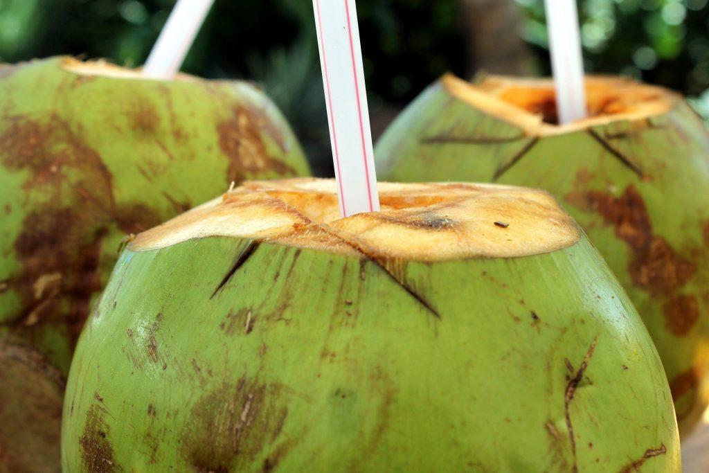Imagem de três cocos verdes com canudos prontos para serem consumidos.