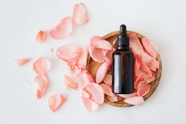 Óleo essencial em cima de pétalas de rosa cor-de-rosa