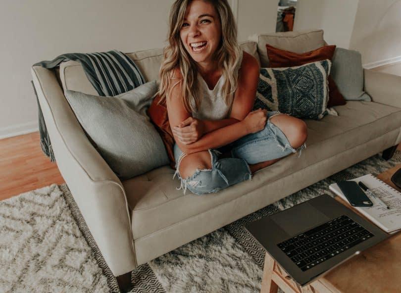 Mulher sentada no sofá de casa olhando para frente e sorrindo