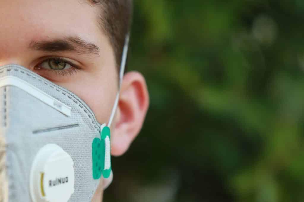 Imagem do rosto de um homem jovem usando uma máscara para se proteger do novo Coranavírus.