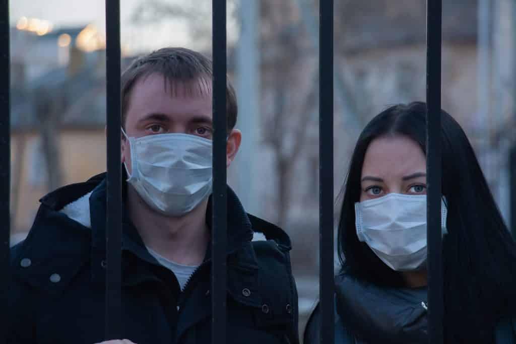 Imagem dos rostos de um casal de homem e mulher atrás de um portão proibidos de sair devido ao novo Coronavírus. Ambos usam máscara.