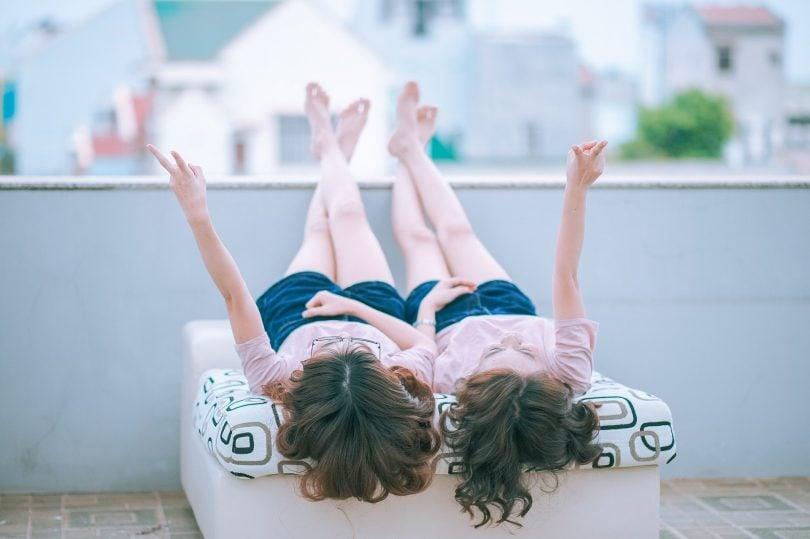 Imagem de duas garotas deitadas sobre uma cama. Elas estão com as pernas para cima contemplando o lindo dia.