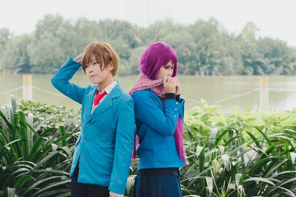 Imagem de um jovem asal oriental em um jardim. Ela usa um cabelo roxo e ele um cabelo avermelhado. Ambos vestem um ter o azul, um uniforme escolar.