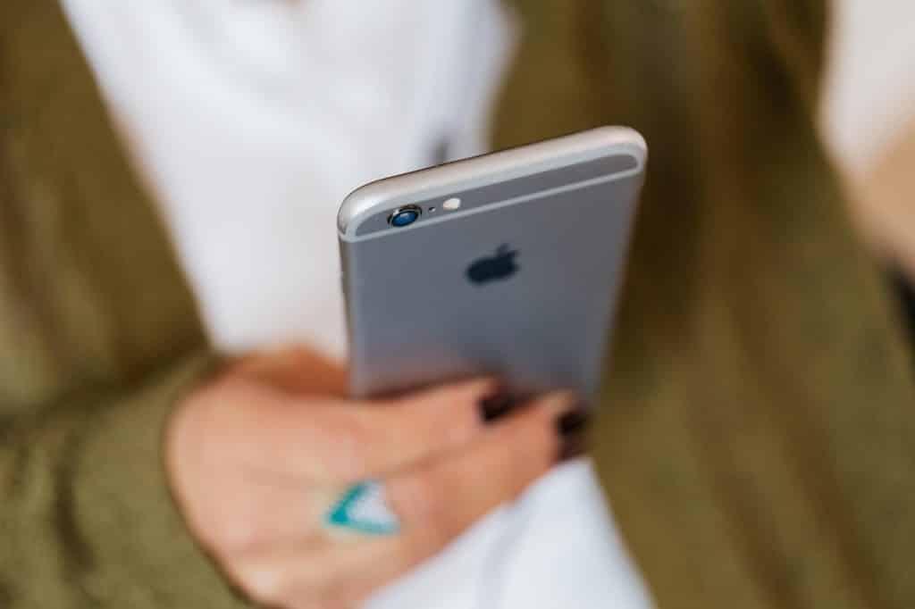 Pessoa com suas unhas pintadas segurando um telefone celular.