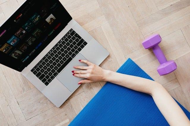 Mão mexendo em notebook com tapete de academia e peso visto do alto