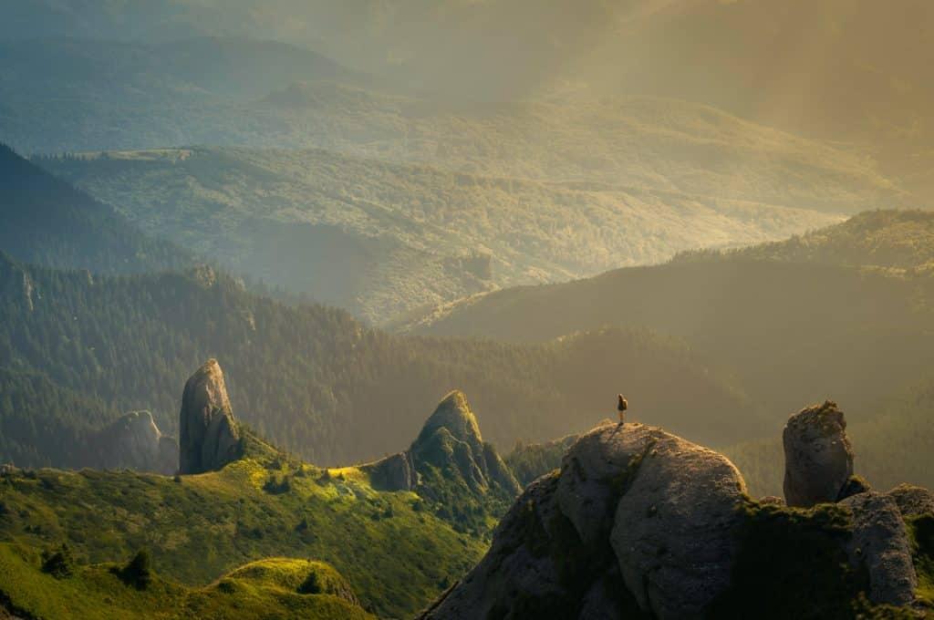 Pessoa sobre uma rocha, de dia, em uma paisagem natural de morros.