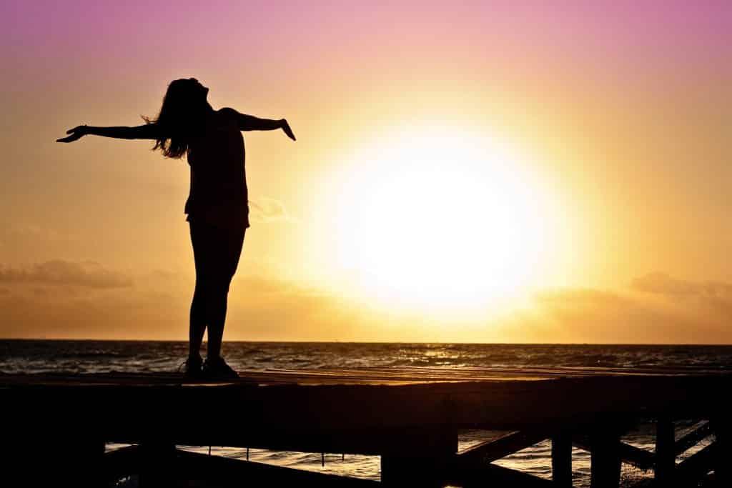 Silhueta de uma mulher de braços abertos ao pôr do sol.