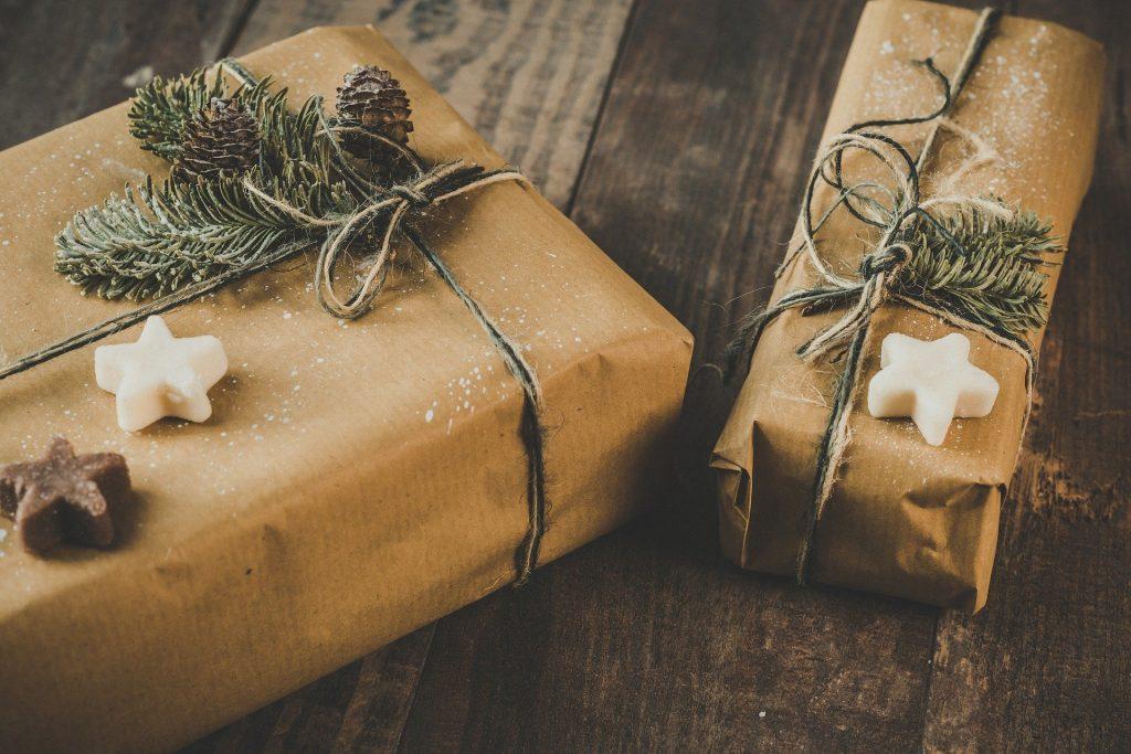 Imagem de duas caixas de presentes embrulhadas em papel pardo e decoadas com enfeites natalinos como estrelas, pinha e folhas da árvore de Natal.