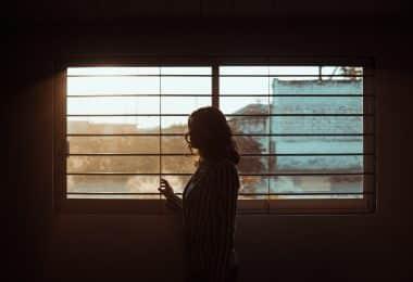 Mulher ao lado da janela olhando para fora