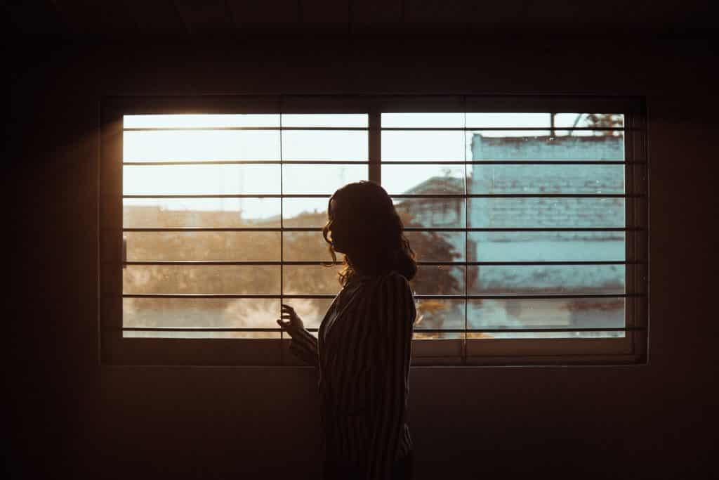 Mulher ao lado de uma janela em um quarto escuro