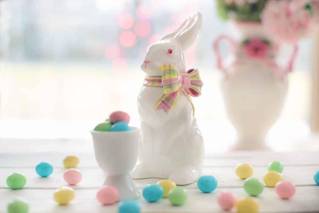 Imagem de um lindo enfeite de porcelana de coelho representando a páscoa.  À sua frente um pequeno pote com gomas de mascar coloridas, fazendo referência aos ovos de páscoa.