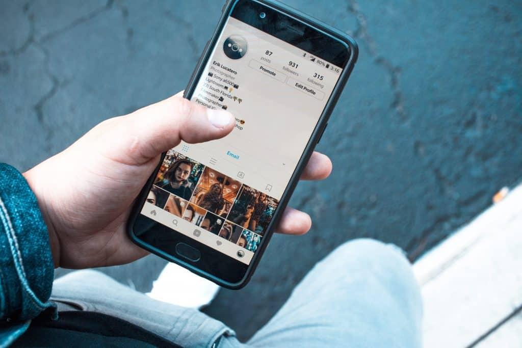 Pessoa segurando celular com o instagram aberto no perfil
