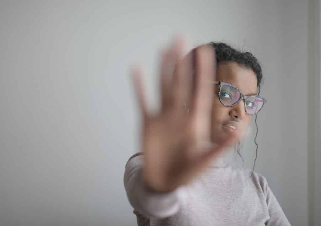 """Mulher com a mão simbolizando """"pare""""."""
