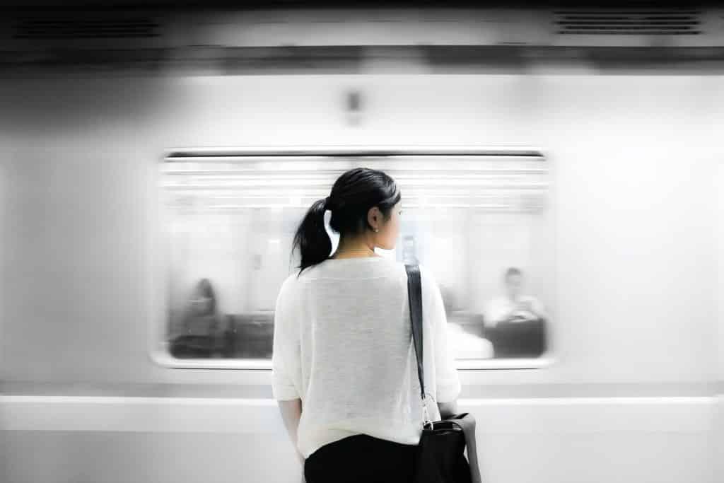 Mulher em pé, vista de costas, olhando para o lado enquanto um metrô passa a sua frente.