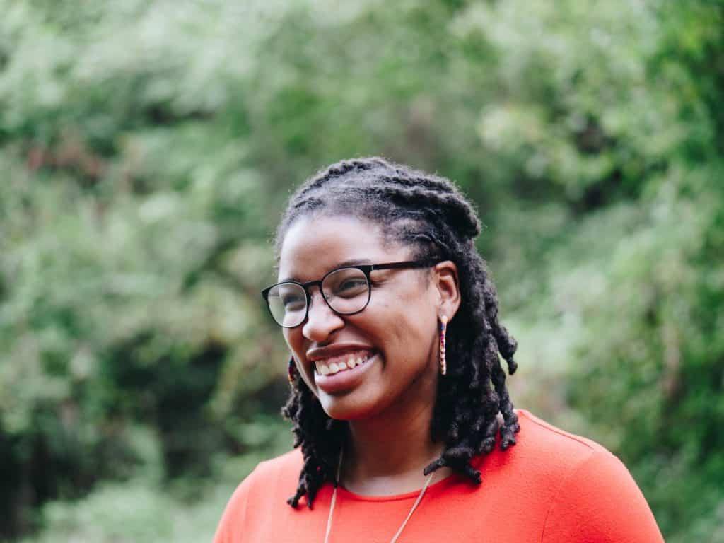 Mulher de óculos sorrindo em meio a um parque com árvores, olhando para o lado.