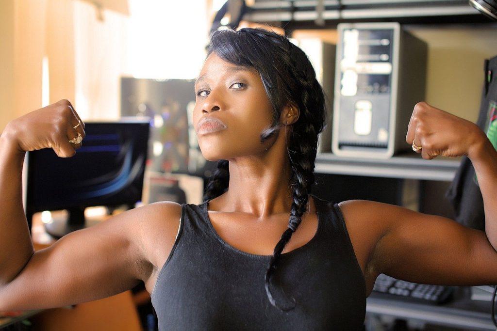 Imagem de uma linda mulher negra mostrando os seus músculos, represetando a força e a igualdade de gênero.