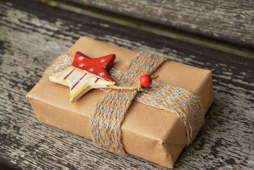 Imagem de uma caixa de presente embrulhada em papel bardo com uma decoração de estrela natalina sobre ela.