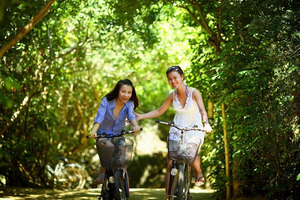 Imagem de duas amigas orientais andando de bicicleta no meio de uma floresta. Elas estão alegres e conseguiram um tempo para estarem juntas e fazer o que mais gostam.