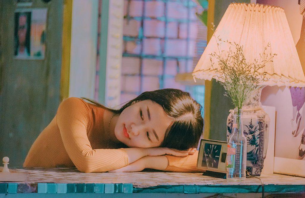 Imagem de uma jovem garota oriental sentada e debruçada em uma bancada. Ao lado dela um abajur aceso. Ela parece estar com uma angústia incontrolável.