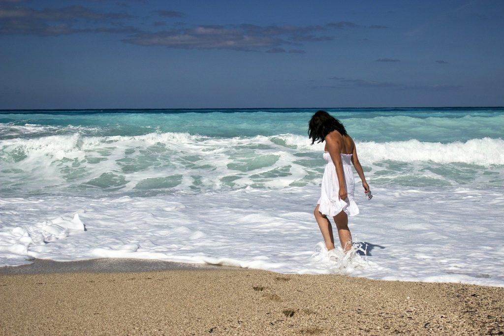 Imagem de um garota usado um vestido branco. Ela está caminhando na praia próximo ao mar. Ela aparenta está feliz, sozinha e com a autoestima elevada.