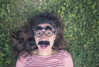 Imagem divertida de uma mulher deitada sobre um gramado. Ela usa um óculos gigante, um bigodão e uma sobrancelha enorme. Ela está muito alegre e com a autoestima elevada.